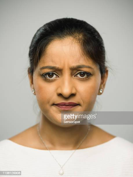 real indian young woman with upset expression looking at camera - frowning stock pictures, royalty-free photos & images