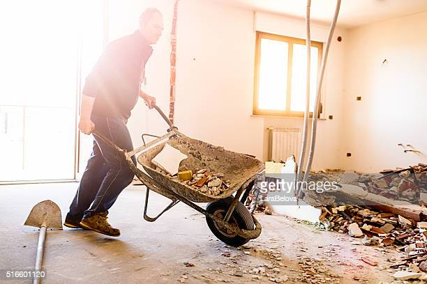 real italian worker repairing apartment - wheelbarrow stock photos and pictures