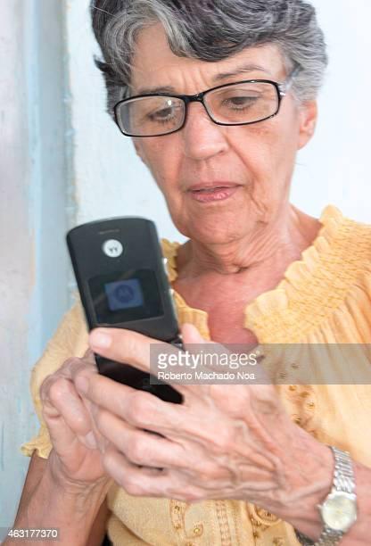 Real life senior Cuban woman using a cellular phone
