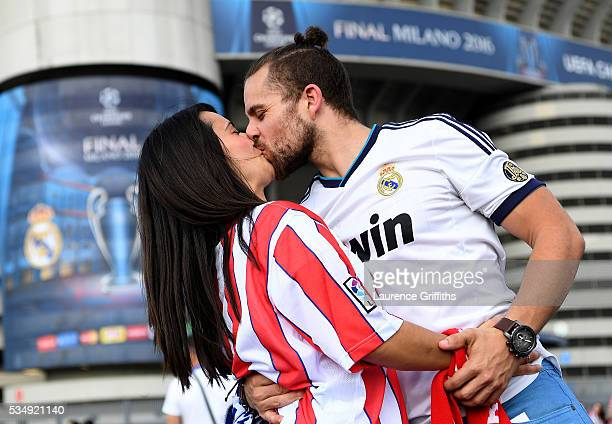 Real Madrid and Club Atletico de Madrid fan kiss each other during the UEFA Champions League Final match between Real Madrid and Club Atletico de...