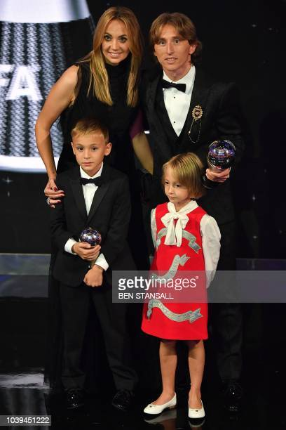 Real Madrid and Croatia midfielder Luka Modric poses with his wife Vanja and their children Ivano and Ema after he wins the trophy for the Best FIFA...