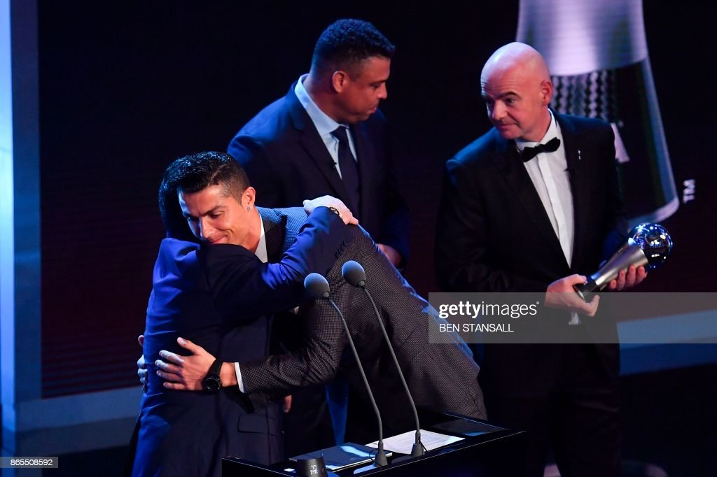 Real Madrid and Portugal forward Cristiano Ronaldo (2nd L) embraces Argentina's former player Diego Maradona (L) as he wins The Best FIFA Men's Player of 2017 Award during The Best FIFA Football Awards ceremony, on October 23, 2017 in London.