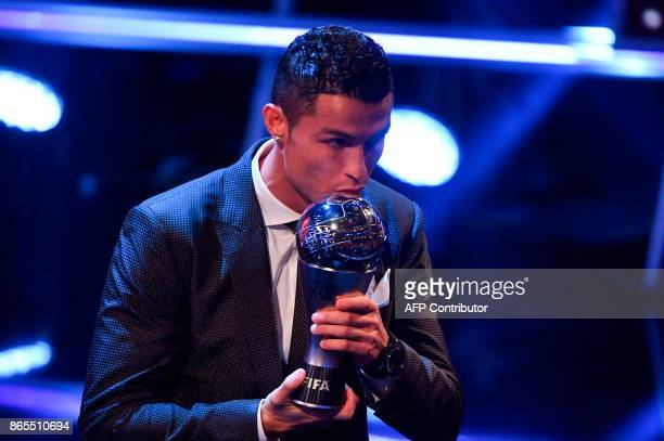 TOPSHOT Real Madrid and Portugal forward Cristiano Ronaldo kisses the trophy after winning The Best FIFA Men's Player of 2017 Award during The Best...