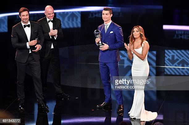 Real Madrid and Portugal's forward and winner of The Best FIFA Mens Player of 2016 Award Cristiano Ronaldo poses on stage with his trophy next to...