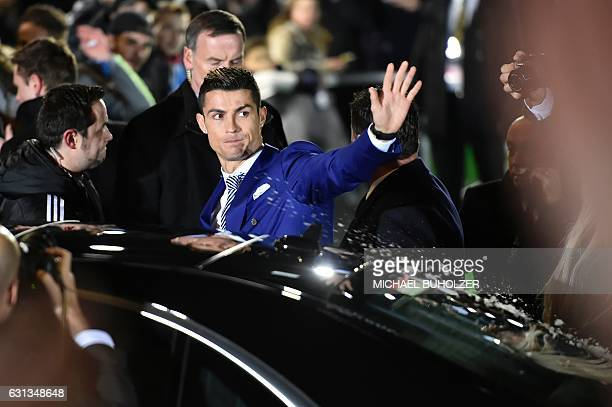 Real Madrid and Portugal's forward and winner of The Best FIFA Mens Player of 2016 Award Cristiano Ronaldo waves as an onlooker throws an object at...