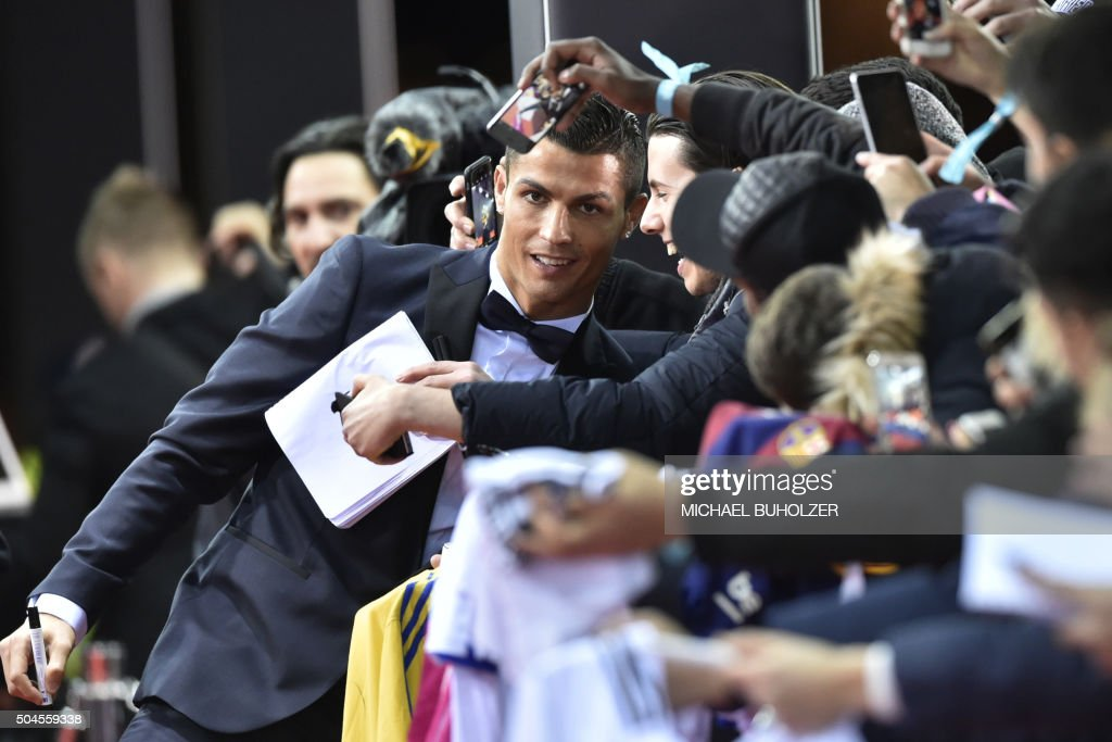TOPSHOT - Real Madrid and Portugal's forward Cristiano Ronaldo poses with fans on the red carpet as he arrives for the 2015 FIFA Ballon d'Or award ceremony at the Kongresshaus in Zurich on January 11, 2016.