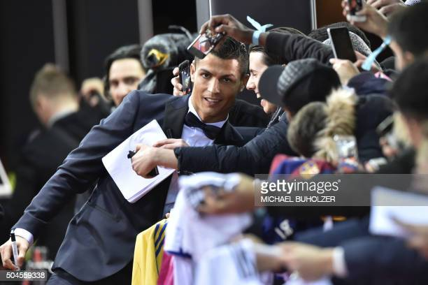 TOPSHOT Real Madrid and Portugal's forward Cristiano Ronaldo poses with fans on the red carpet as he arrives for the 2015 FIFA Ballon d'Or award...