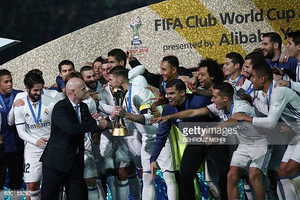Real Madrid captain and defender Sergio Ramos holds receives the trophy as players celebrate on the podium after winning the Club World Cup football...