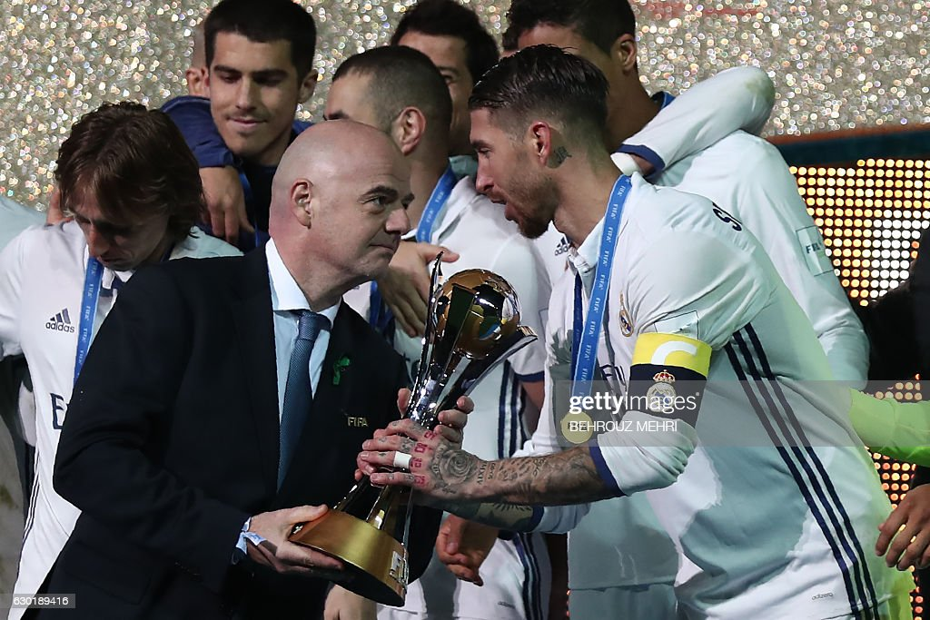 Real Madrid captain and defender Sergio Ramos holds receives the trophy from FIFA president Gianni Infantino as players celebrate on the podium after winning the Club World Cup football final match against Kashima Antlers of Japan at Yokohama International stadium in Yokohama on December 18, 2016. / AFP / Behrouz MEHRI