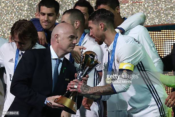 Real Madrid captain and defender Sergio Ramos holds receives the trophy from FIFA president Gianni Infantino as players celebrate on the podium after...