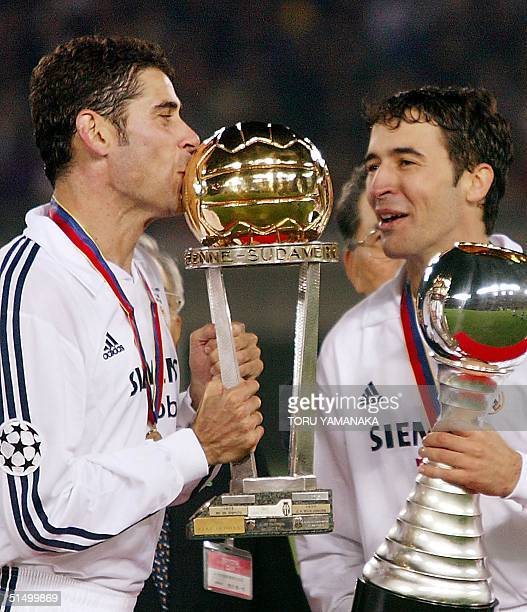 Real Madrid captain Ferando Ruiz Hierro kisses the Intercontinental Cup as he shares a joy with foward Raul Gonzalez holds the Toyota Cup during...