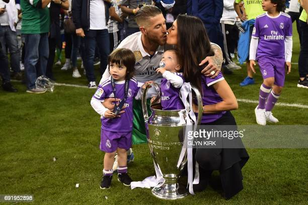 TOPSHOT Real Madrid captain Sergio Ramos his wife Pilar Rubio and their sons Sergio and Marco pose with the trophy after Real Madrid won the UEFA...