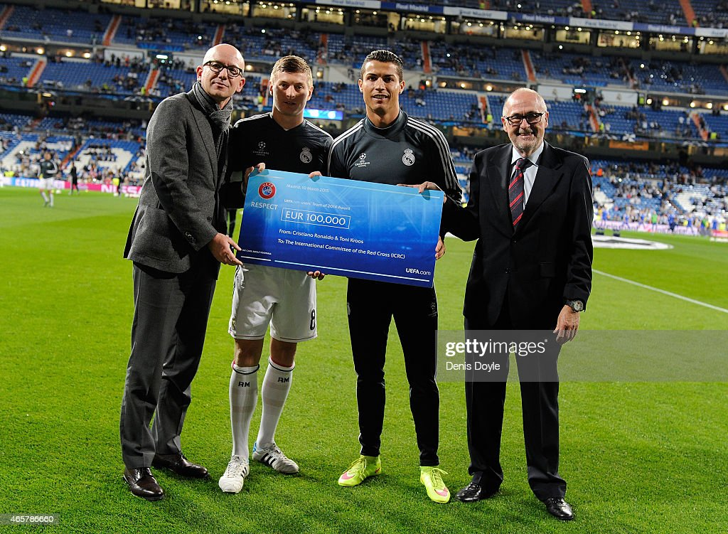 Real Madrid CF's Toni Kroos and Cristiano Ronaldo together with UEFA Executive Committee member Peter Gillieron (R) hand over a cheque to Yves D'Accord, Director General of the International Committee of the Red Cross, at the Santiago Bernabeu stadium on March 10, 2015 in Madrid, Spain. Real Madrid CF play Schalke 04 later in their UEFA Champions League Last of 16, Second Leg match.