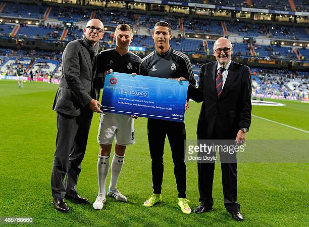 Real Madrid CF's Toni Kroos and Cristiano Ronaldo together with UEFA Executive Committee member Peter Gillieron hand over a cheque to Yves D'Accord...