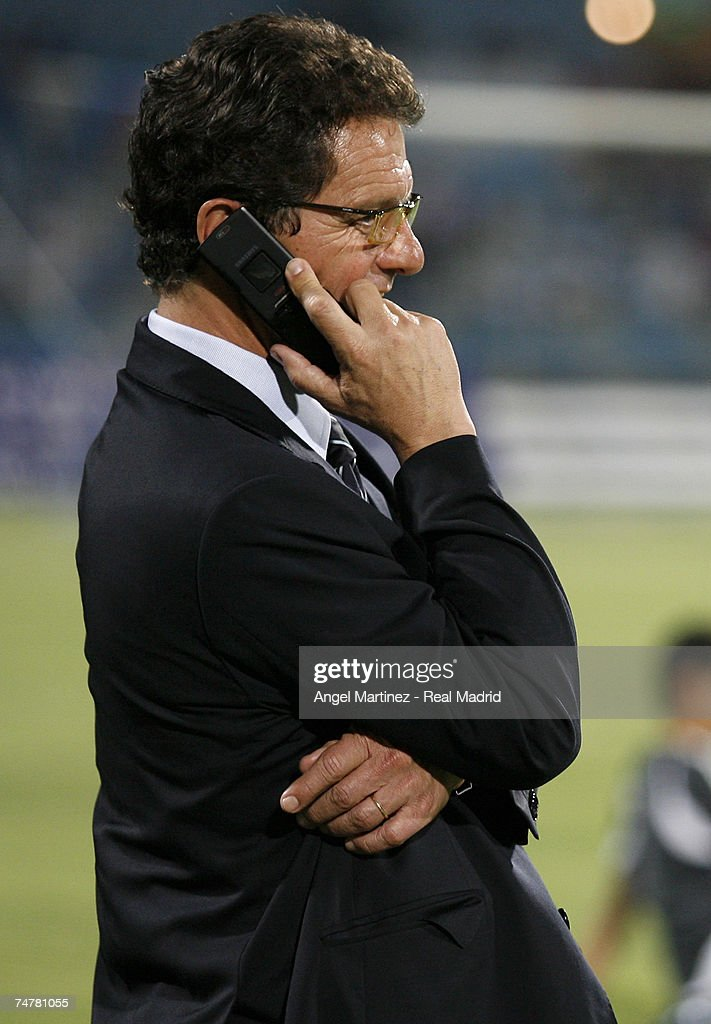 Real Madrid coach Fabio Capello talks on his mobile phone before the friendly match between Real Madrid and a Palestinian & Israeli XI at the Ramat Gan stadium on June 19, 2007 in Tel Aviv, Israel