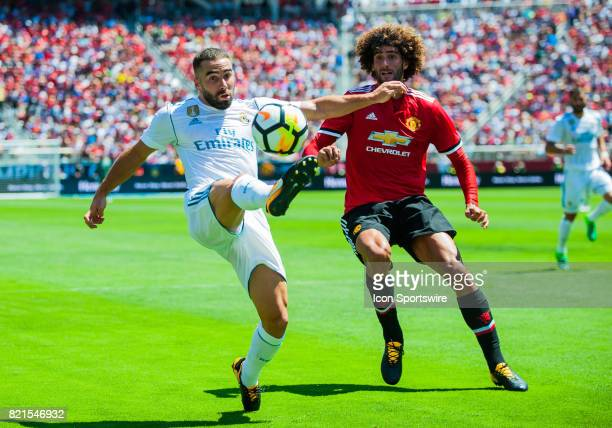 Real Madrid defender Daniel Carvajal tries to take control of a ball while being guarded by Manchester United midfielder Marouane Fellaini during the...