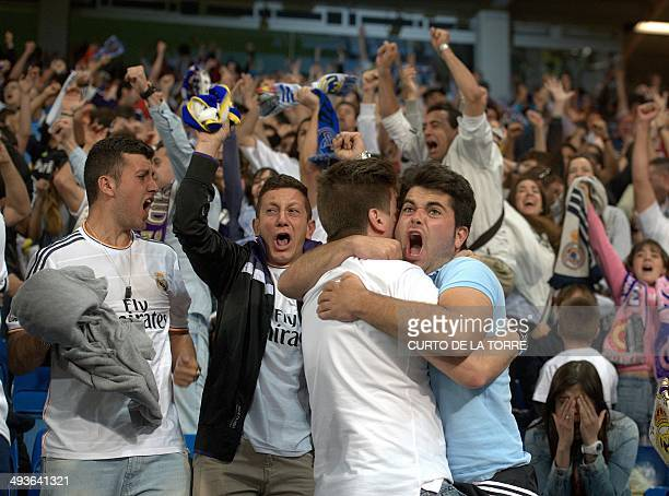 Real Madrid fans celebrate a team goal as they watch on a big screen at the Santiago Bernabeu stadium in Madrid on May 24 2014 the UEFA Champions...