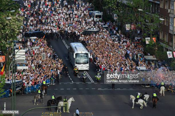 Real Madrid fans cheer their team as their coach arrives at Estadio Santiago Bernabeu outdoors before the UEFA Champions League Quarter Final second...