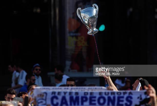 A Real Madrid football team fan holds a balloon with the shape of the Champions League trophy during celebrations for their team's victory at the...
