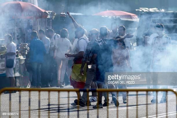 Real Madrid football team fan walk through flare smoke outside the Santiago Bernabeu stadium in Madrid on June 3 2017 during the UEFA Champions...