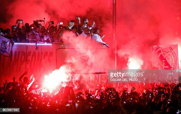 Real Madrid football team fans surround the bus as Real Madrid players hold up the trophy celebrating the team's win on Plaza Cibeles in Madrid on...