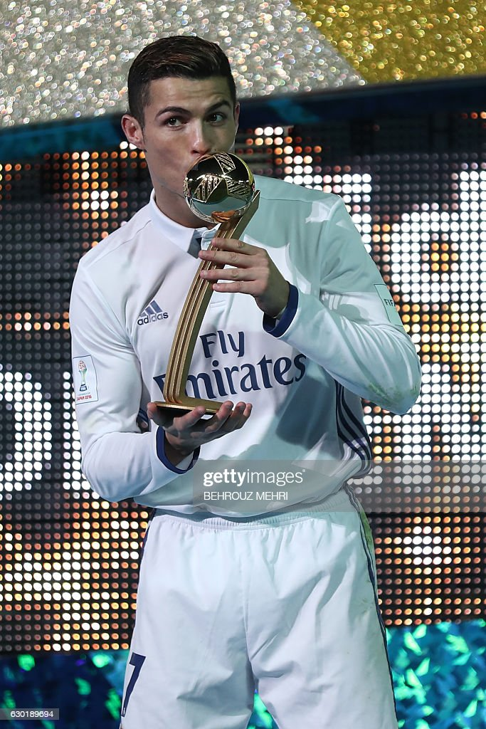 Real Madrid forward Cristiano Ronaldo receives the Golden Ball trophy after winning the Club World Cup football final match against Kashima Antlers of Japan at Yokohama International stadium in Yokohama on December 18, 2016. / AFP / Behrouz MEHRI