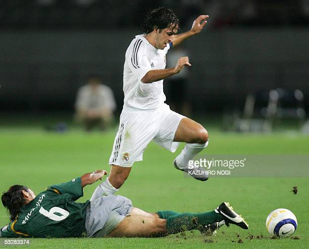 Real Madrid forward Raul Gonzalez keeps the ball as he jumps over Japan's Tokyo Verdy 1969 midfielder Kazuyuki Toda during their football match at...