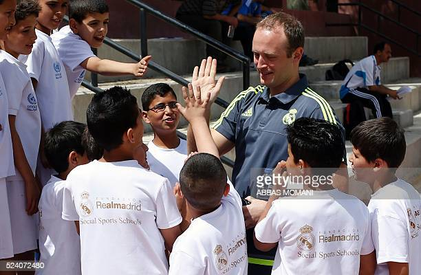 Real Madrid Foundation's technical director David Gil Chapado gives a high five to Palestinian children during a training session with Palestinian...