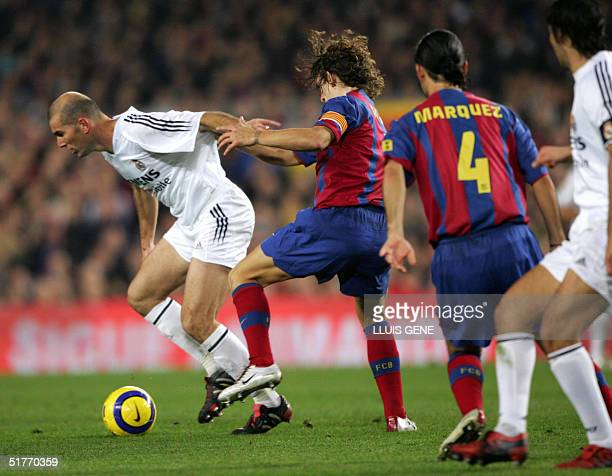 Real Madrid French Zinedine Zidane vies with FC Barcelona's Carles Puyol and Mexican Rafael Marquez in a Spanish League match at Camp Nou stadium in...