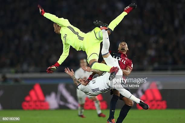 TOPSHOT Real Madrid goalkeeper Keylor Navas collides teammate Sergio Ramos and Kashima Antlers midfielder Fabricio during the Club World Cup football...