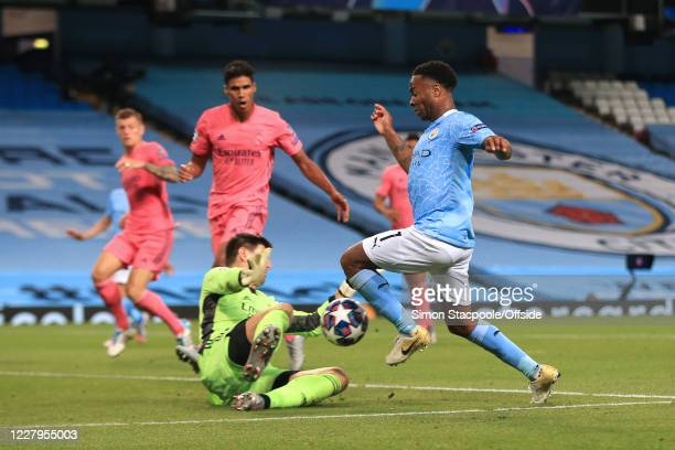 Real Madrid goalkeeper Thibaut Courtois slides out to challenge Raheem Sterling of Man City during the UEFA Champions League round of 16 second leg...