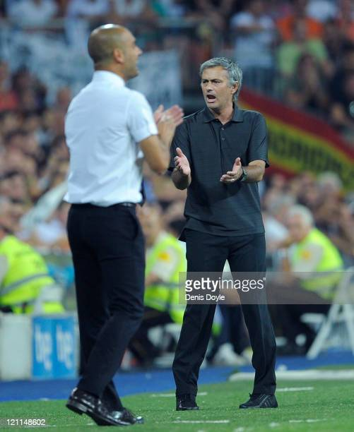 Real Madrid head coach Jose Mourinho applauds beside Barcelona head coach Josep Guardiola during the Super Cup first leg match between Real Madrid...