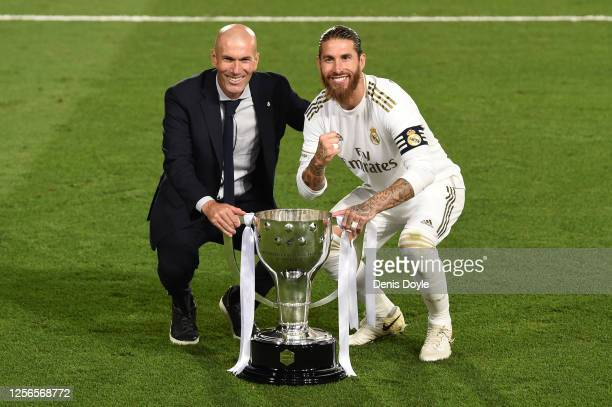 Real Madrid head coach Zinedine Zidane and captain Sergio Ramos pose with the La Liga trophy after Madrid secure the La Liga title during the Liga...