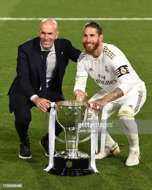 Real Madrid head coach Zinedine Zidane and captain Sergio Ramos pose with the La Liga trophy after Madrid secure the La Liga title during the Liga...