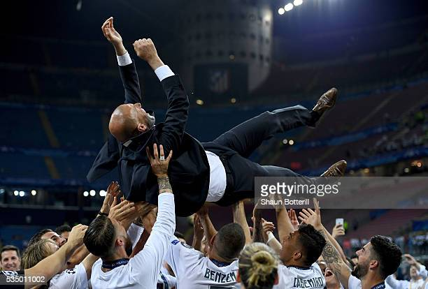 Real Madrid head coach Zinedine Zidane is thrown in the air after the UEFA Champions League Final match between Real Madrid and Club Atletico de...