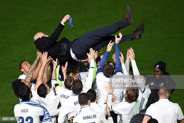 TOPSHOT Real Madrid head coach Zinedine Zidane is thrown into the air by Real Madrid players after winning the Club World Cup football final match...