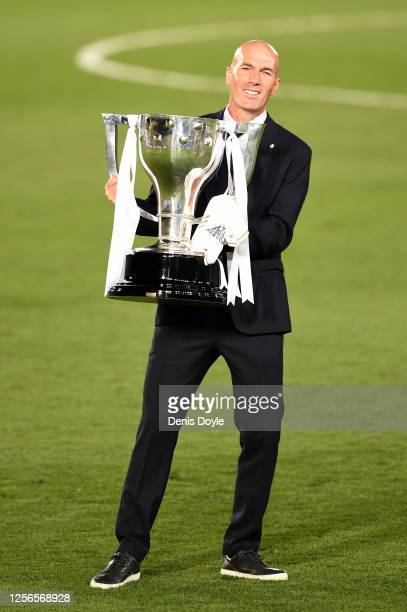 Real Madrid head coach Zinedine Zidane poses with the La Liga trophy after Madrid secure the La Liga title during the Liga match between Real Madrid...