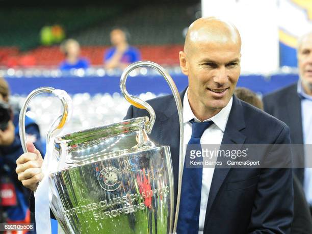 Real Madrid manager Zinedine Zidane poses with the UEFA Champions League trophy during the UEFA Champions League Final match between Juventus and...