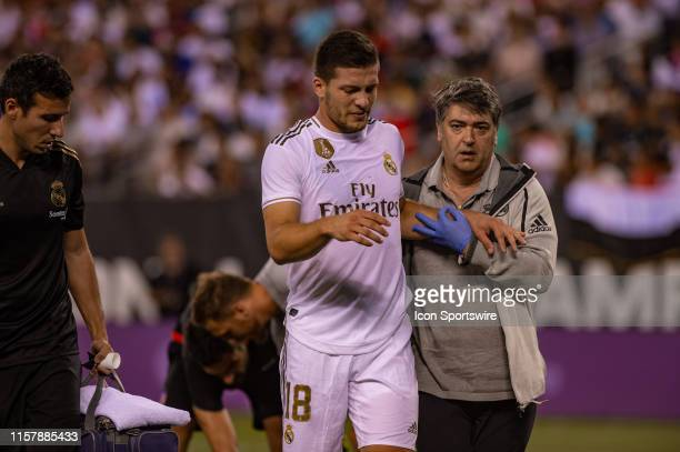 Real Madrid midfielder Luka Jovic is helped from the field after suffering an injury during the International Champions Cup friendlies match between...
