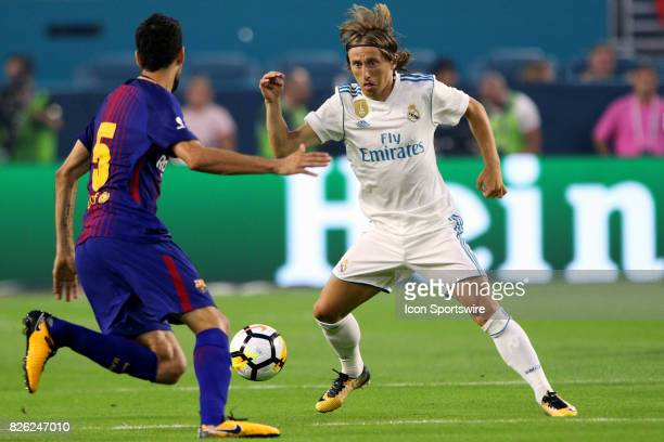 Real Madrid midfielder Luka Modric and Barcelona midfielder Sergio Busquets battle for the ball during the first half of the International Champions...