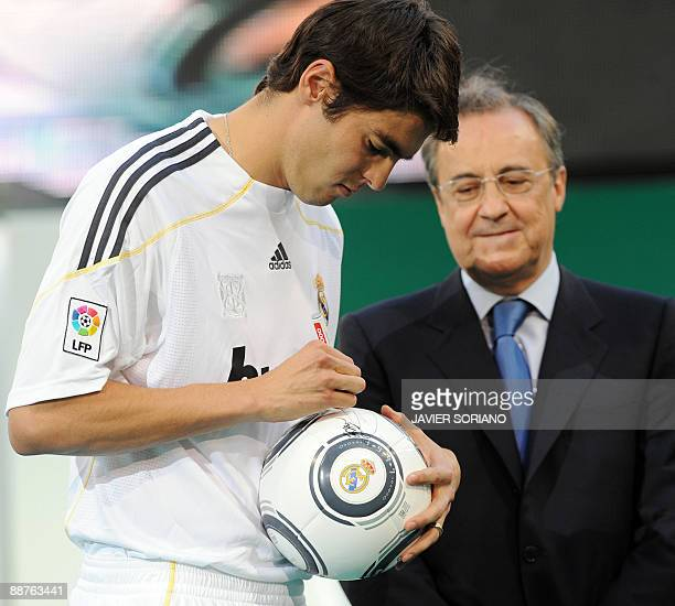 Real Madrid new player Brazilian midfielder Kaka signs a football ball next to Real Madrid president Florentino Perez during his official...