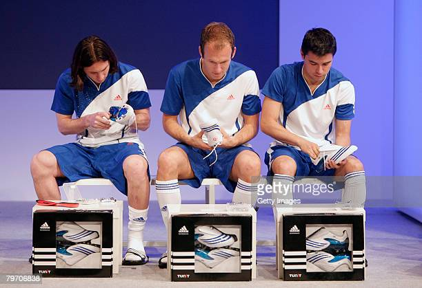 Real Madrid player Arjen Robben sits in between Barcelona players Lionel Messi and Saviola as they assemble their new shoes during the adidas F50...