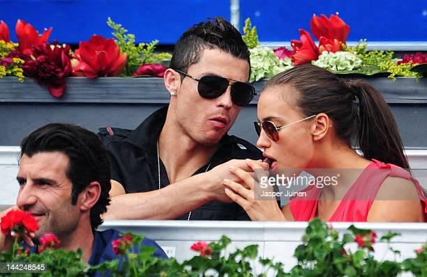 Real Madrid player Cristiano Ronaldo feeds his girlfriend Irina Shayk a piece of chocolate as Portuguese football legend Luis Figo looks on while...