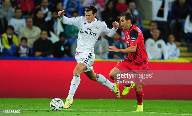 Real Madrid player Gareth Bale outpaces Fernando Navarro of Seville during the UEFA Super Cup match between Real Madrid and Sevilla FC at Cardiff...