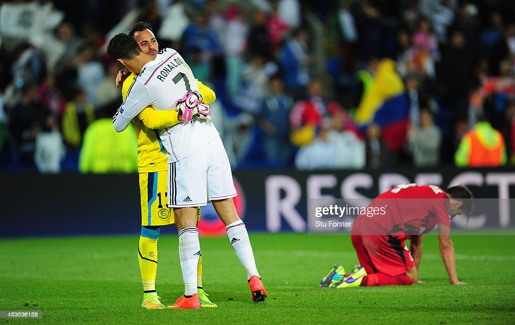 Real Madrid player Ronaldo consoles Sevilla goalkeeper Beto as Grzegorz Krychowiak (r) looks on after the UEFA Super Cup match between Real Madrid and Sevilla FC at Cardiff City Stadium on August 12, 2014 in Cardiff, Wales.