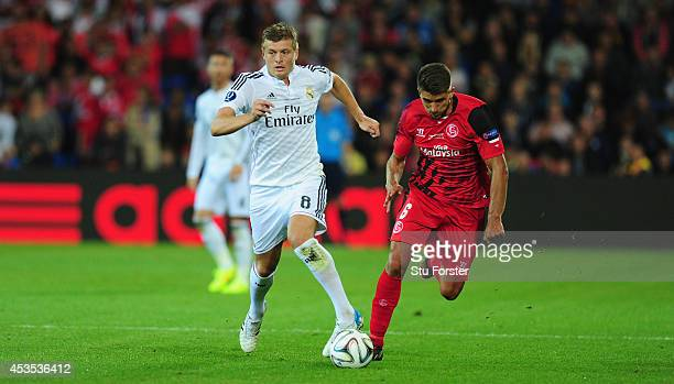 Real Madrid player Toni Kroos outpaces Daniel Carrico of Seville during the UEFA Super Cup match between Real Madrid and Sevilla FC at Cardiff City...