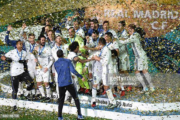 Real Madrid Players and staff celebrate on the podium after winning the Club World Cup football final match against Kashima Antlers of Japan at...