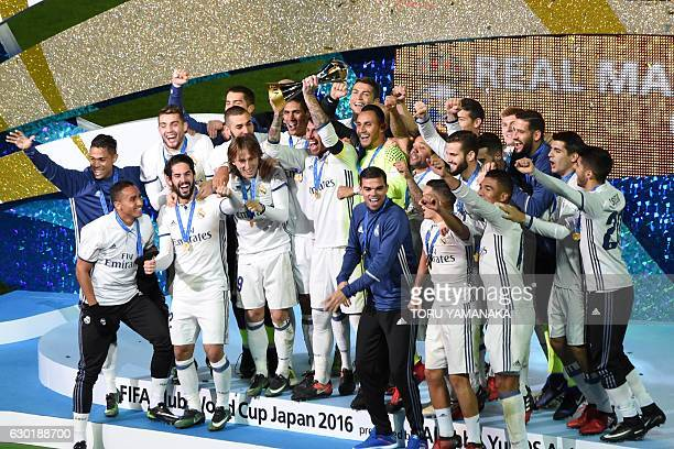 Real Madrid Players and staff celebrate with their trophy after winning the Club World Cup football final match against Kashima Antlers of Japan at...