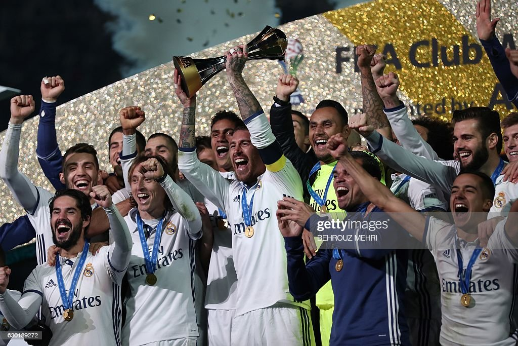 Real Madrid players and staff celebrate with their trophy after winning the Club World Cup football final match against Kashima Antlers of Japan at Yokohama International stadium in Yokohama on December 18, 2016. / AFP / Behrouz MEHRI