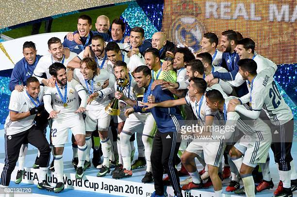 Real Madrid players and staff celebrate with their trophy after winning the Club World Cup football final match between Kashima Antlers of Japan and...